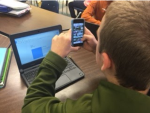 Searching photos on a phone while writing on a Chromebook.